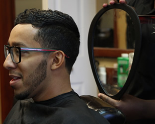 man being shown haircut through mirror